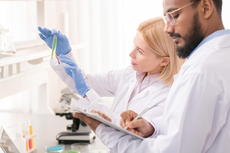 Team of scientists in laboratory. Team of scientists in lab coats standing in laboratory and doing research together while working with chemical liquid and data stock photo