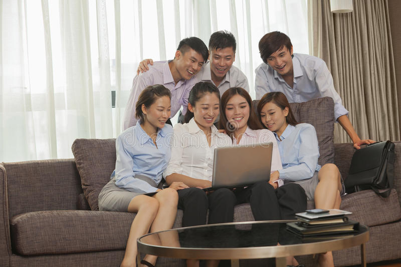 Download Team Of Smiling Business People Working Together And Looking At One Laptop Stock Image - Image: 31127631