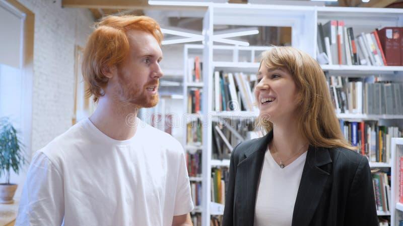 Team Smiling While creativo joven que tiene una conversación en oficina fotos de archivo