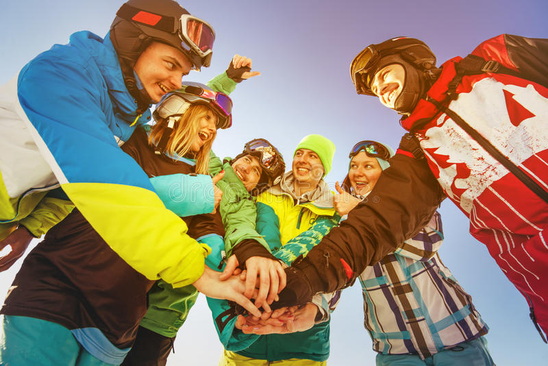 Team of snowboarders stands on blue sky backdrop in mountains royalty free stock photo