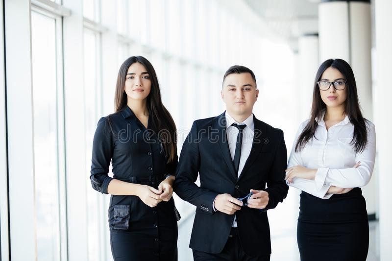 Team standing in office hall, team leader in front. The business people walk in the office hall on the sun background. The business people walk in the office royalty free stock photos