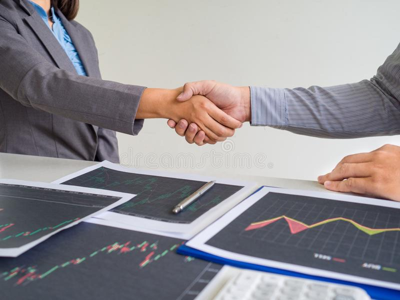 Team of stock trader discuss graph report and shake hands deal on online trading guidelines. Set targets for online trading management success royalty free stock images