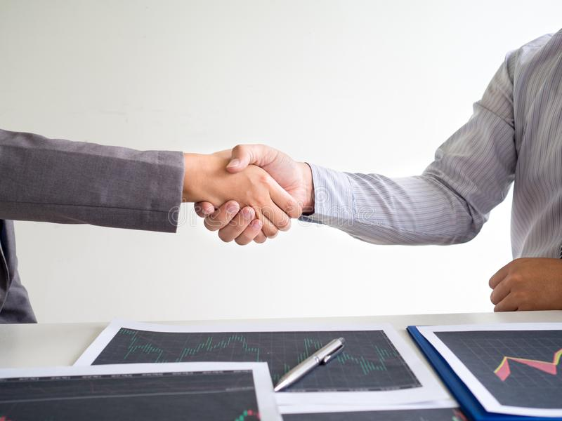 Team of stock trader discuss graph report and shake hands deal on online trading guidelines, set targets for online trading. Management success stock image