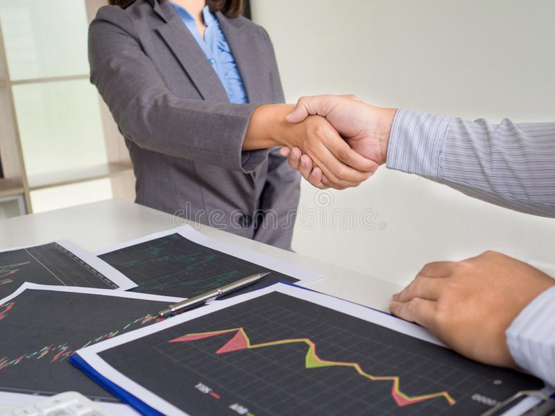 Team of stock trader discuss graph report and shake hands deal on online trading guidelines. Set targets for online trading management success stock photography