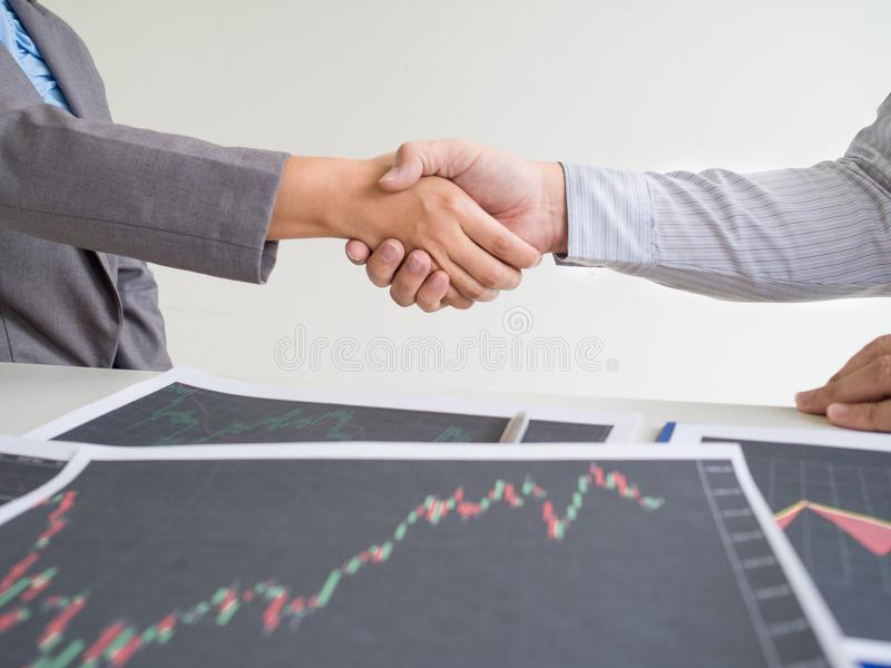 Team of stock trader discuss graph report and shake hands deal on online trading guidelines. Set targets for online trading management success stock image