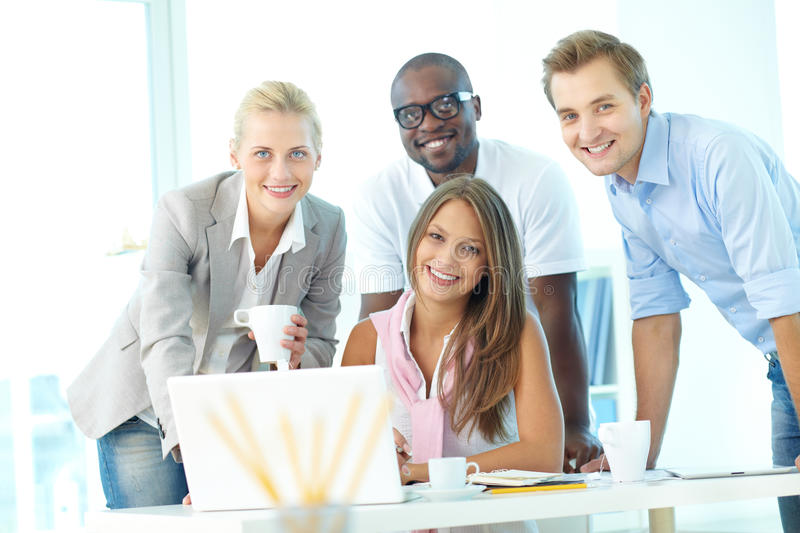 Team of students. Group of friendly students or businesspeople looking at camera at workplace stock images