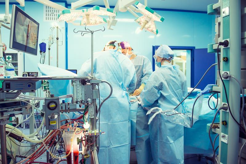Team of surgeon in uniform perform operation on a patient using laparoscopic equipment at modern cardiac surgery clinic. royalty free stock photos