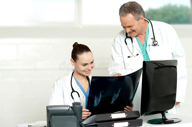 Team of surgeons discussing x-ray report. In their chamber. All looks fine in report royalty free stock image