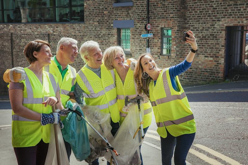 Team Takes a Selfie. A group of five people taking a selfie. They are wearing high visibility jackets and are participating in a city clean-up royalty free stock image