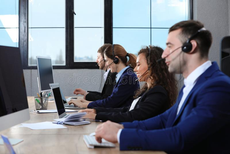 Team of technical support with headsets. At workplace stock image