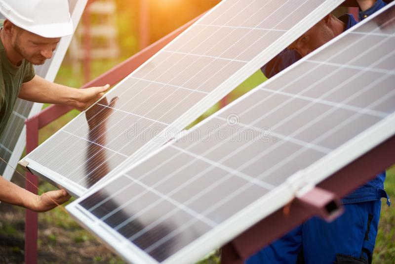 Installation of stand-alone exterior photo voltaic panels system. Renewable green energy generation. Team of technicians adjusting big shiny solar panel to stock photos