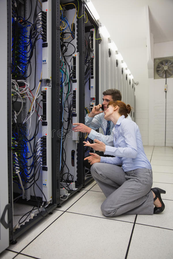 Team of technicians kneeling and looking at servers royalty free stock image