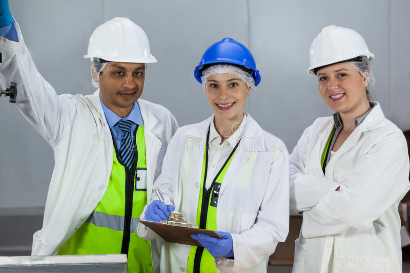 Team of technicians standing in meat factory. Portrait of technicians standing in meat factory royalty free stock image