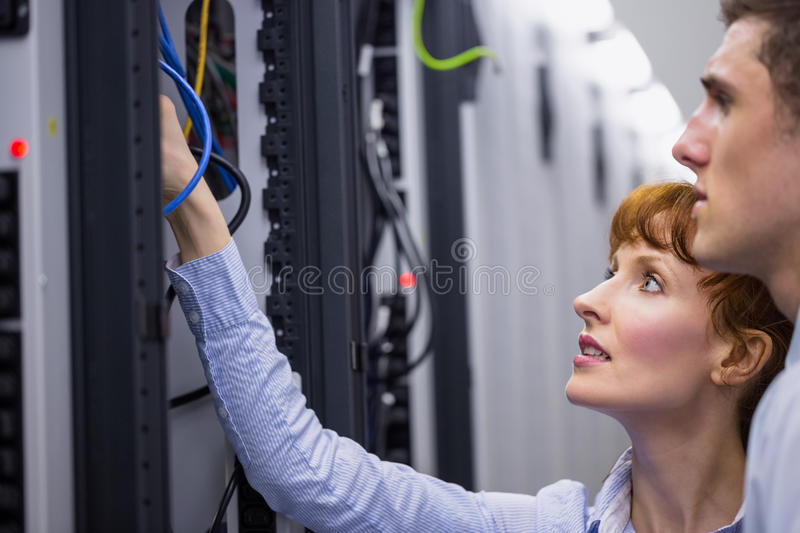 Team of technicians talking and looking at server stock photography