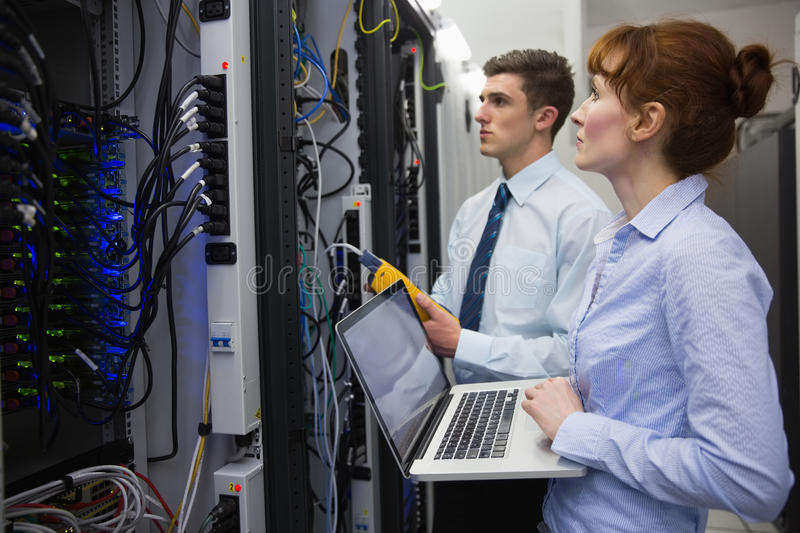 Team of technicians using digital cable analyser on servers royalty free stock photo