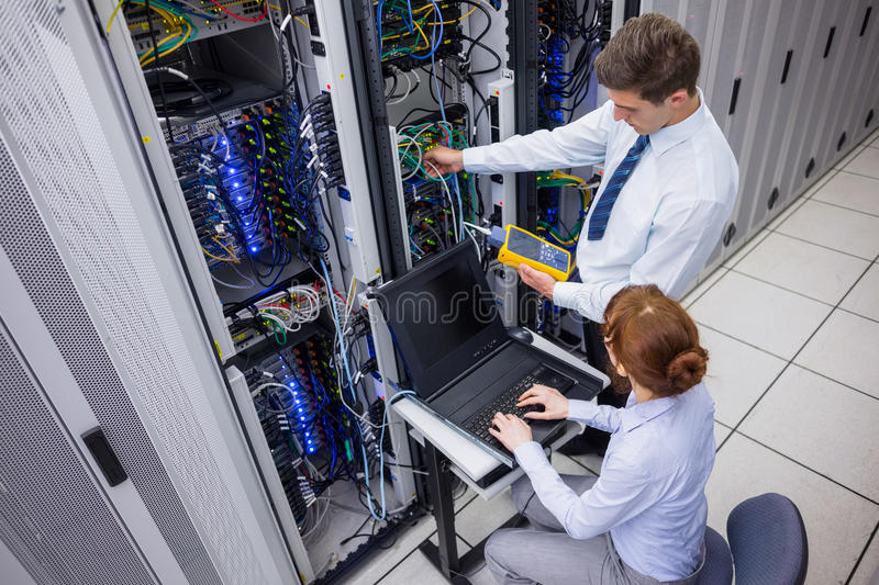 Team of technicians using digital cable analyser on servers royalty free stock image