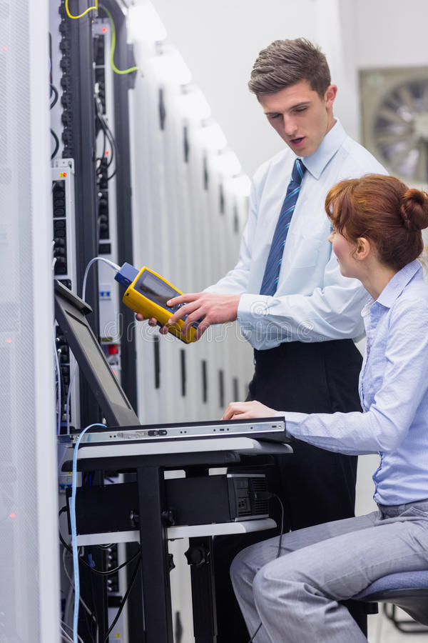 Team of technicians using digital cable analyser on servers stock photos