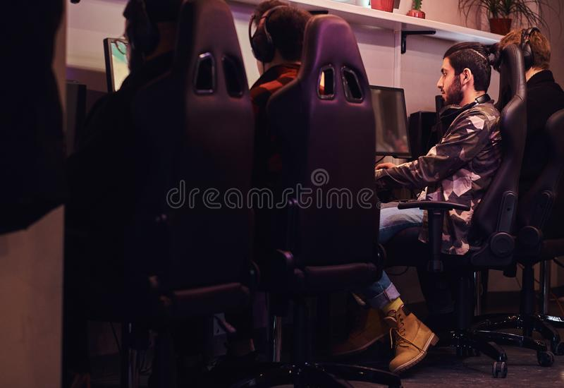 Team of teenage gamers plays in a multiplayer video game on pc in a gaming club. A team of teenage gamers plays in a multiplayer video game on pc in a gaming royalty free stock image