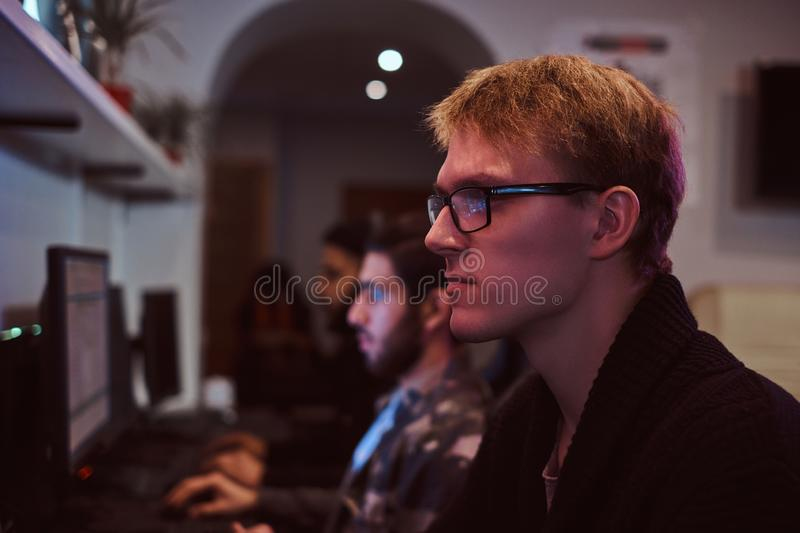 Team of teenage gamers plays in a multiplayer video game on pc in a gaming club. A team of teenage gamers plays in a multiplayer video game on pc in a gaming stock photography