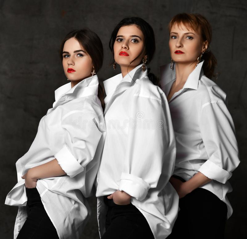 Team of three brutal and stylish woman in white mens shirts posing as the poster of the movie or music band. Team of three brutal and stylish women in white mens royalty free stock photo
