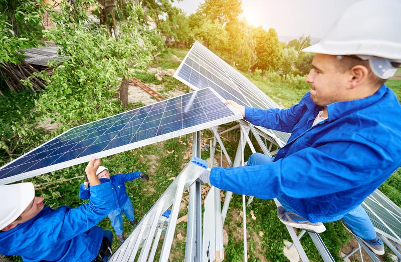 Installing of solar photo voltaic panel system. Team of three technicians mounting photo voltaic panel to stand-alone solar system platform on bright sunny day royalty free stock photography