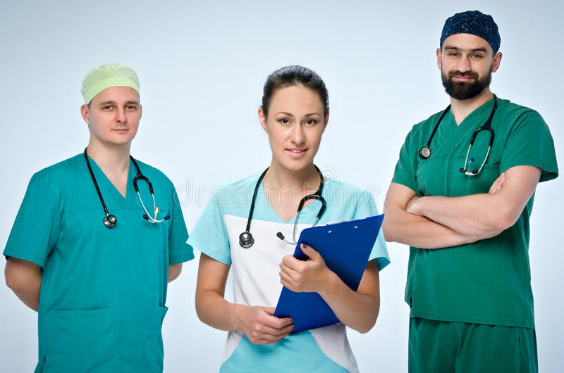 A team of three young doctors. The team included a doctor and a woman, two men doctors. They are dressed in scrubs. On the necks royalty free stock images