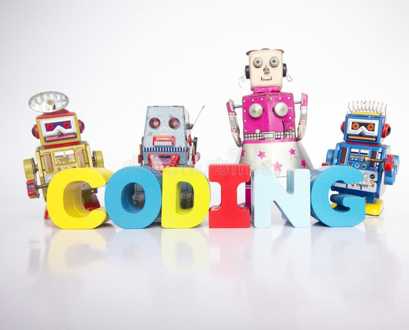 A team of toy robots with the word coding isolated. On white royalty free stock photos