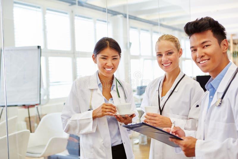 Team tussen verschillende rassen van artsen in medische school stock afbeelding