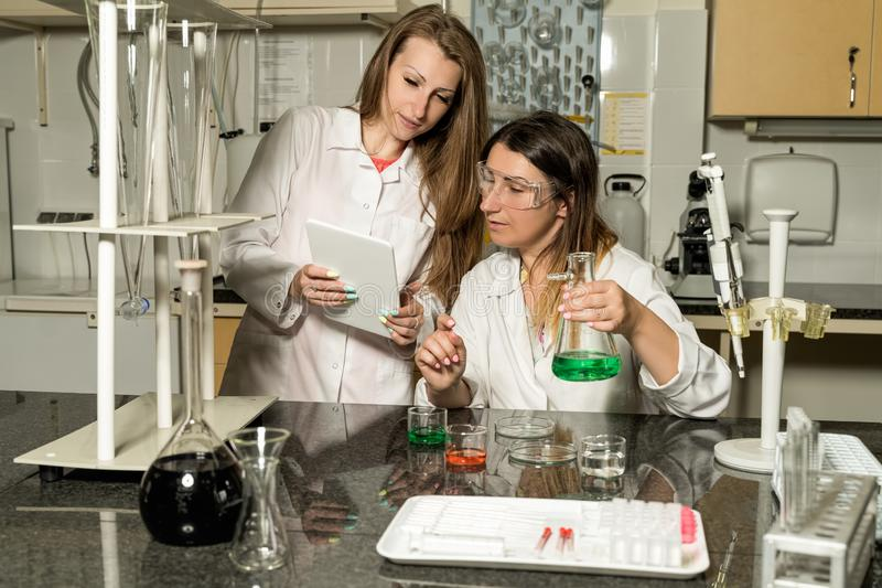 Team of two female laboratory technicians working in chemical or pharmaceutical laboratory royalty free stock image
