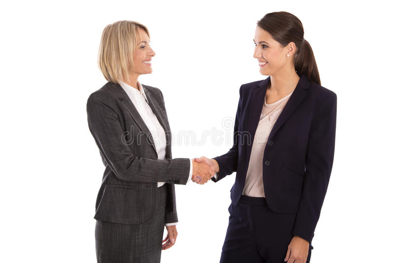 Team: Two isolated businesswoman shaking hands wearing business royalty free stock photos