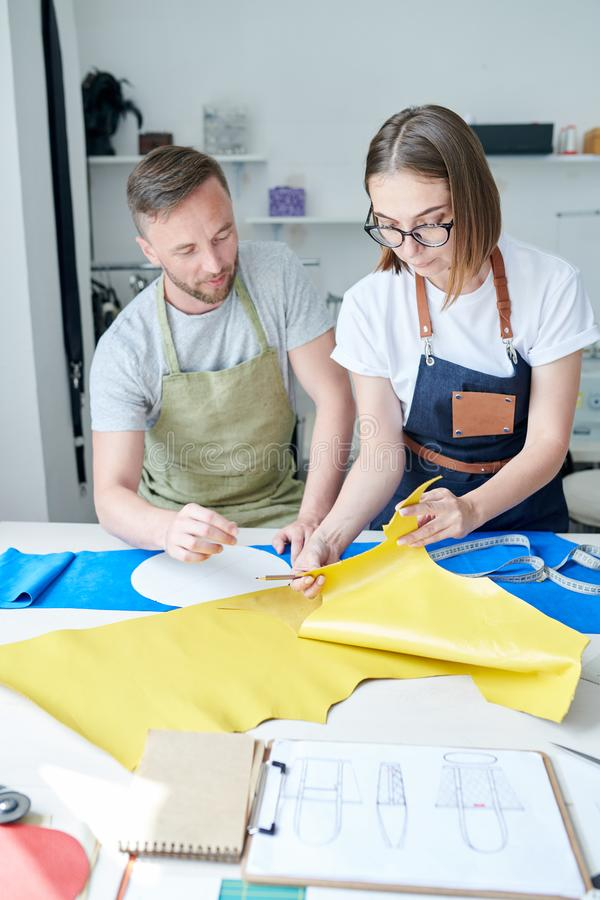 People working with leather fabric. Team of two tanners working at the table with leather fabric and creating new product royalty free stock image