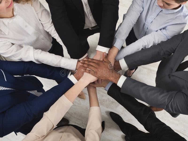 Team of united coworkers standing with hands together royalty free stock images