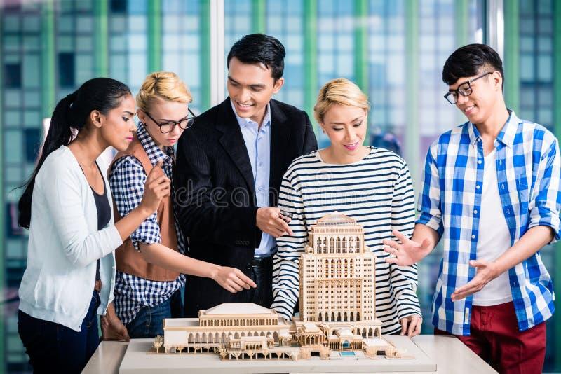 Team van architecten die modelbouw voorstellen royalty-vrije stock afbeeldingen