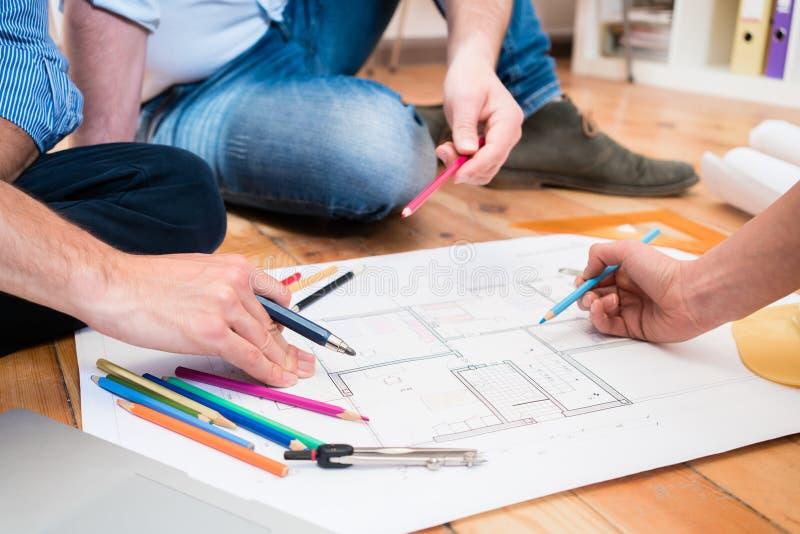 Team van architecten die op vloer met bouwplannen zitten stock foto's