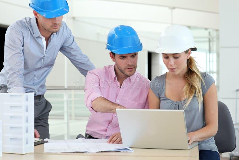 Team van architecten met helmen die op kantoor werken stock foto