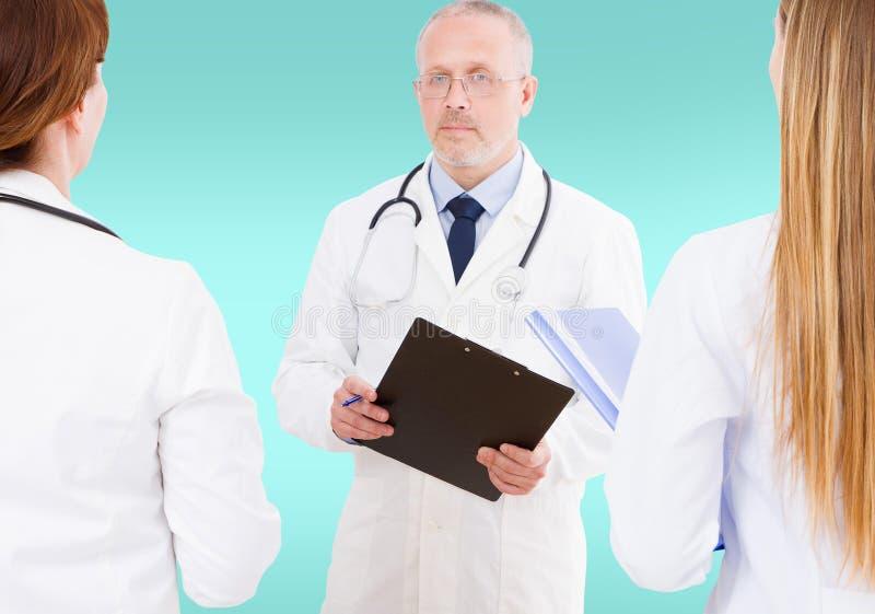 Team van artsen die iets bespreken omhoog geïsoleerd op blauwe achtergrond, spot stock fotografie