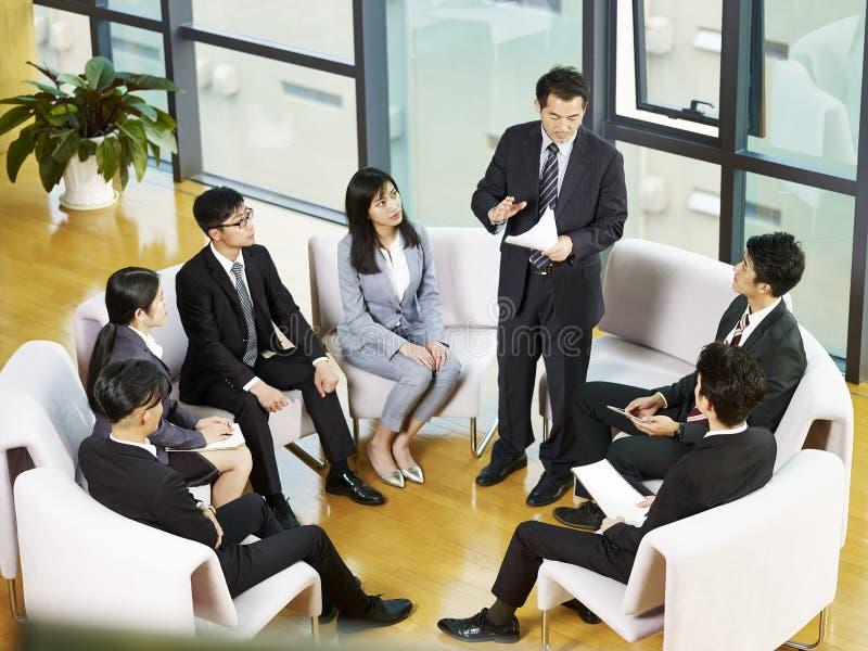 Team van Aziatische bedrijfsmensen die in bureau samenkomen stock afbeelding