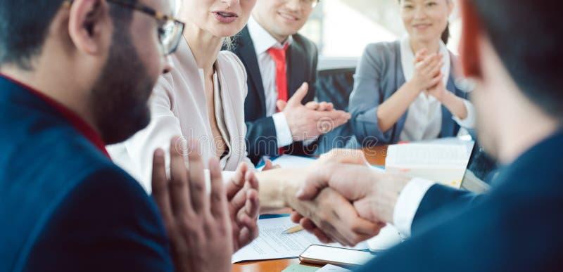 Team van bedrijfsmensen die een overeenkomst bespreken die de overeenkomst sluiten royalty-vrije stock foto