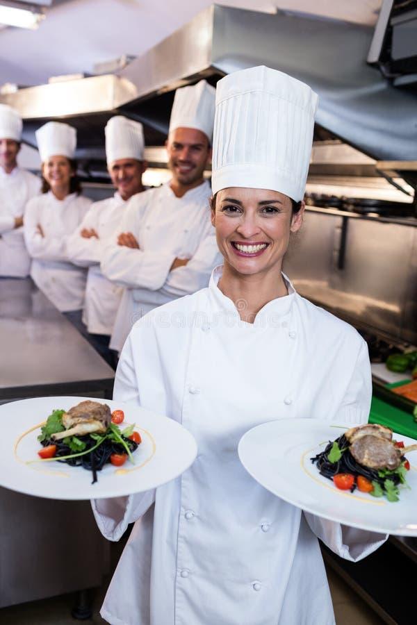 Team van chef-koks met één die schotels voorstellen royalty-vrije stock afbeelding