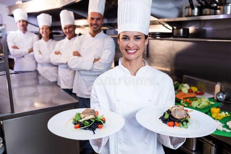 Team van chef-koks met één die schotels voorstellen royalty-vrije stock fotografie