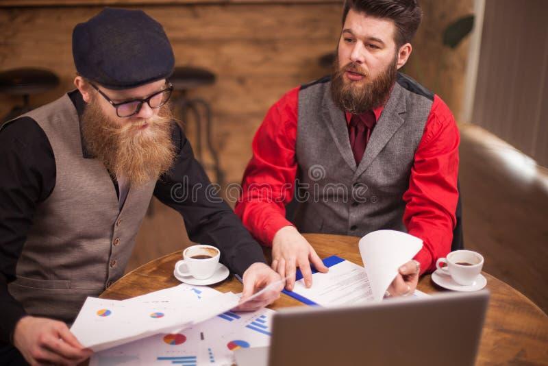 Team van collega's die in de bar werken en technologie gebruiken stock afbeeldingen