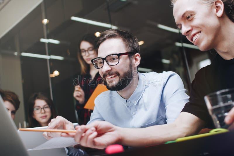 Team van de vrolijke collega'swerken aangaande moderne gadgets Bemanning van medewerkers die het werkvergadering in zolderbureau  royalty-vrije stock foto