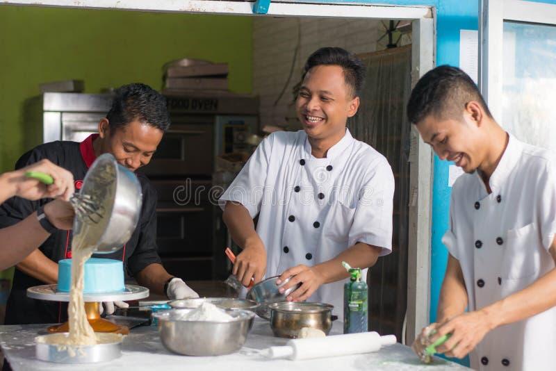 Team van het Aziatische mannelijke gelukkige werk van de gebakjechef-kok samen terwijl het eparing beslag van PR stock afbeeldingen