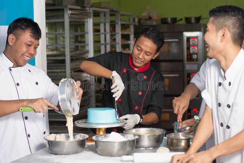 Team van het Aziatische mannelijke gelukkige werk van de gebakjechef-kok samen terwijl het voorbereiden van beslag stock afbeelding