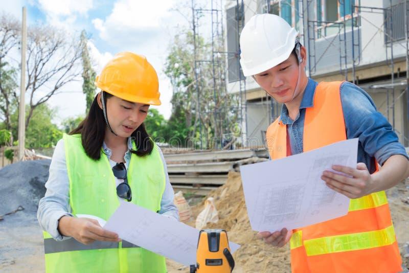 Team van ingenieurs die gele helm dragen en bij bouwwerf werken stock foto