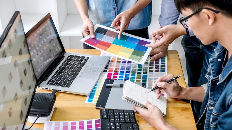 Team van jonge collega's creatieve grafische ontwerper die aan kleurenselectie werken en op grafiektablet op het werk, Kleur trek royalty-vrije stock afbeeldingen