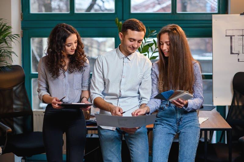 Team van jonge Kaukasische ingenieur die zich dichtbij lijst bevinden terwijl het spreken over nieuw idee over bouwtekeningen in  stock foto