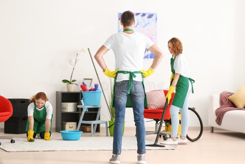 Team van jonge schoonmakende de dienstberoeps op het werk stock foto