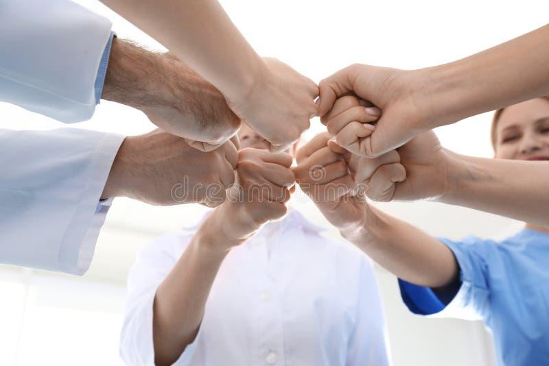 Team van medische artsen die handen op lichte achtergrond samenbrengen Het concept van de eenheid stock afbeeldingen