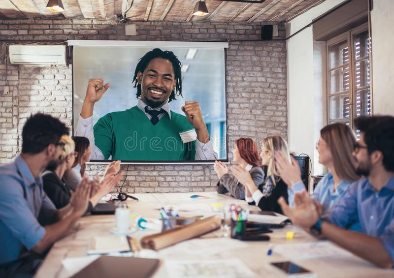 Team van medische studenten die artsentoespraak het projectorscherm bekijken in videoconferentie royalty-vrije stock afbeeldingen